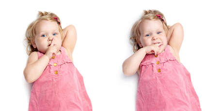 shh: Young little girl with curly hair in pink dress lying and doing shh silence sign over isolated white background