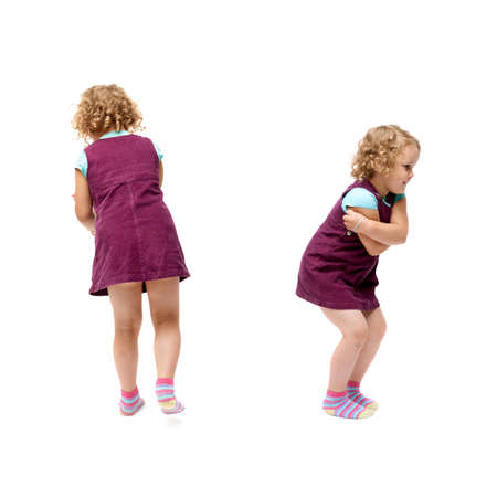 turn away: Young little girl with curly hair in purple dress standing over isolated white background