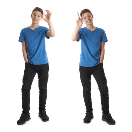 Cute teenager boy in blue T-shirt standing and showing OK victory sign over white isolated background full body