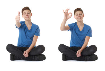 posing  agree: Cute teenager boy showing thumb up OK sign in blue T-shirt and lotus posture over white isolated background