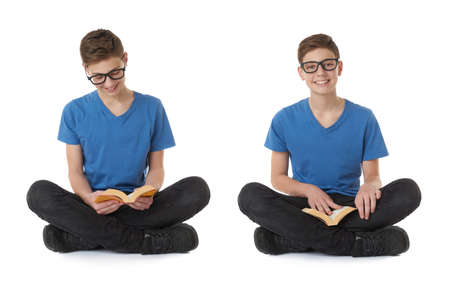 poor eyesight: Cute teenager boy with book in blue T-shirt, glasses and lotus posture over white isolated background Stock Photo