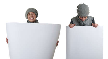 bill board: Set of cute teenager boy in gray sweater, hat and scarf holding paper bill board over white isolated background, half body