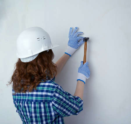 unpainted: Young woman in casual clothes in front of white unpainted wall in white helmet working with hammer, happy people and construction concept