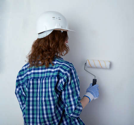 unpainted: Young woman in casual clothes in front of white unpainted wall in white helmet working with paint roller, happy people and construction concept
