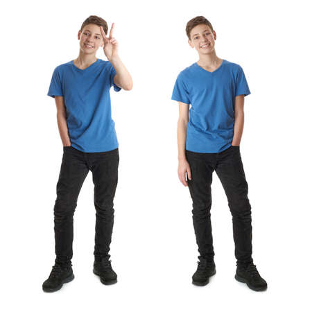 Cute teenager boy in blue T-shirt standing and showing victory sign over white isolated background full body Stock Photo