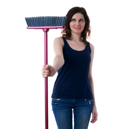 Smiling young woman in dark T-shirt and green rubber gloves over white isolated background holding broom in hands, cleaning and healthy lifestyle concept Stock Photo