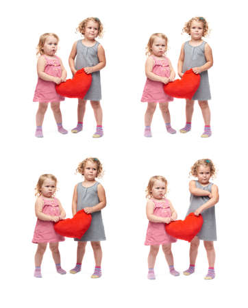 sad heart: Couple of young little girls sisters with curly hair in gray and pink dress holding red plush heart and standing over isolated white background