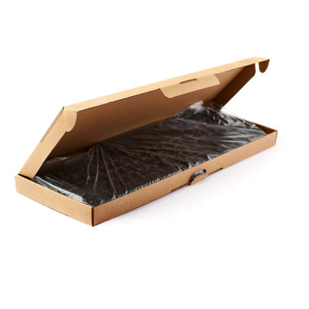 Black computer querty keyboard packed into cardboard box isolated over white background