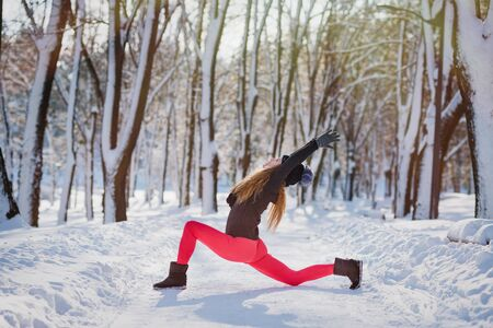 Beautiful woman doing yoga outdoors in the snow at winter time