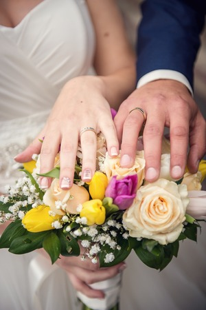 Hands with wedding rings and bouquet from roses