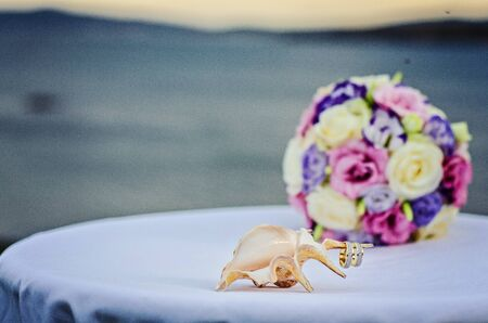 desirable: Yellow pink and purple wedding bouquet from roses. Beach and sea background