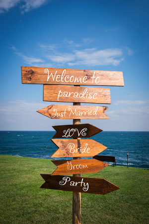romantic places: Picture of wedding wooden direction signpost in front of the sea