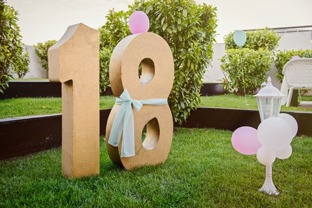 happy 18th birthday: Number eighteen gold color over green grass. Anniversary. Horizontal. Party decoration
