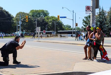 Toronto, OntarioCanada - August 3 2019: Policeman takes photos for tourists at the annual Caribbean Carnival (formerly called Caribana), a free public event celebrating Caribbean culture. Redactioneel