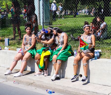 Toronto, OntarioCanada - August 3 2019:  Dancers take a break at the annual Caribbean Carnival (formerly called Caribana), a free public event celebrating Caribbean culture. Redactioneel