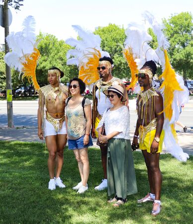 Toronto, OntarioCanada - August 3 2019:  Dancers pose with tourists at the annual Caribbean Carnival (formerly called Caribana), a free public event celebrating Caribbean culture.