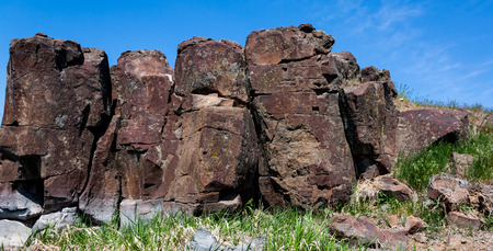Red desert rocky hillside with rough cracked stones and grass Stock Photo