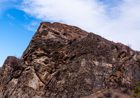 Red desert stone peak with blue sky and clouds