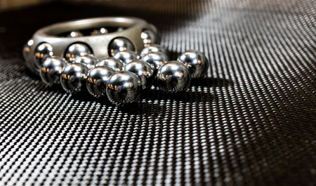 Loose ball bearings in front of an automotive wheel bearing on carbon fiber cloth. Foto de archivo