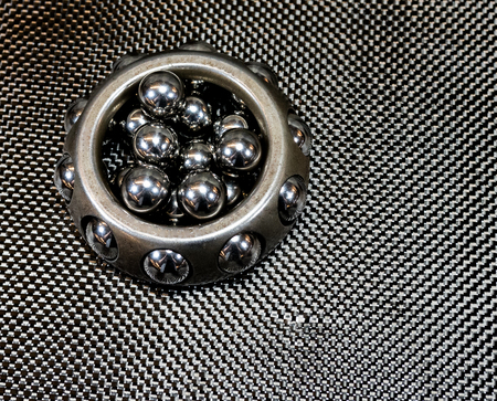 Antique automotive vintage wheel bearing with loose ball bearings on plain weave carbon fiber