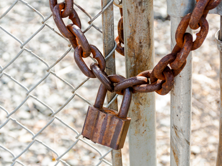Old rusty heavy duty pad lock and chain on a fence and gate junction in the say