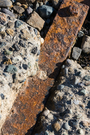 Rusty iron bar impregnated between rocky concrete blocks with a bolt visible 스톡 콘텐츠