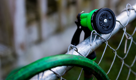 Green garden hose nozzle on a fence near an over hanging hose Stock Photo