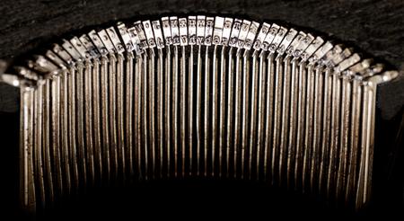 Old well worn antique typewriter key striker set isolated on a black background