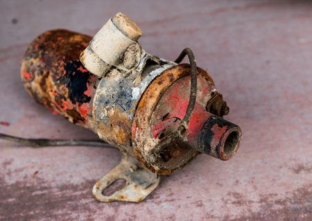Vintage antique automotive ignition coil with bracket and suppression condenser with orange rust and red peeling paint Stock Photo