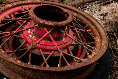 Vintage antique automotive wire wheel spokes and hub with red peeling paint and rust and oxidation Stock Photo