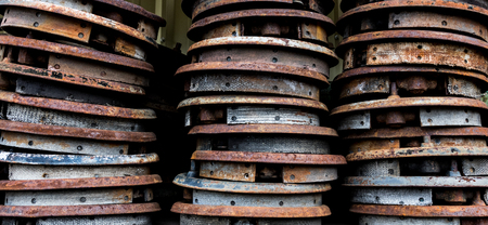Vintage antique automotive brake shoes connected to backing plates in a pile at a wrecking yard.