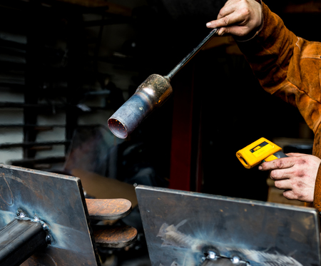 Metal worker preheating steel plates with a propane torch in preparation for welding and heat Stock Photo