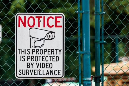 Notice private property video surveillance sign on chain link fence with icon Stock Photo