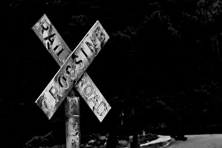 Old vintage retro distressed railroad crossing sign with worn faded text on black