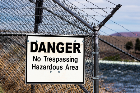 Dangerous no trespassing hazardous ares white sign on a barbed wire chain link fence with a river