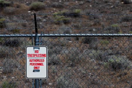 No trespassing authorized personnel sign on a chain link barbed wire fence with dry bushes Stock Photo