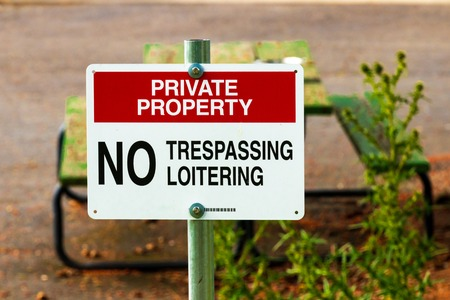 Private property no trespassing sign on a post with a picnic table Stock Photo