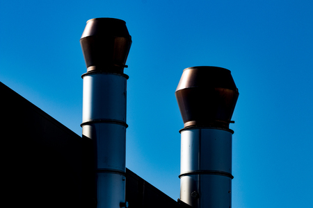 Industrial external air ventilation duct exhaust vents with a blue sky Stock Photo
