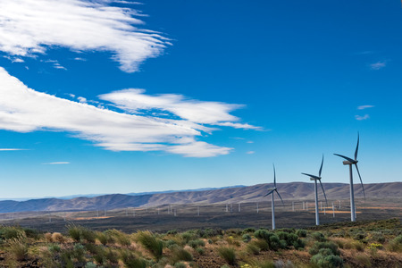 Green sustainable energy windmill power turbine electricity generators on rolling hills with clouds and blue sky above Banco de Imagens