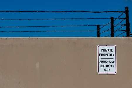 Concrete wall with a private property sign and barbed wire and a blue sky