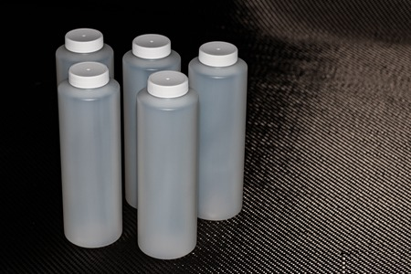 White plastic containers with lids on carbon fiber background Stock Photo
