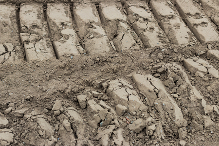 ATV tire tracks side by side in the dirt deeply textured