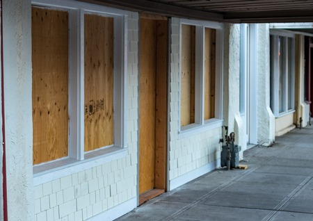 Retail storefront closed and boarded up with plywood Stock Photo