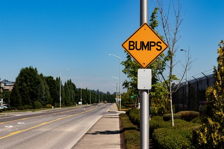 Bumps road sign next to an industrial byway and a blue sky Stock Photo
