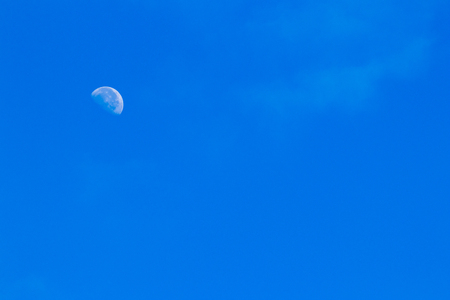 Partial moon against a blue morning sky with haze and clouds