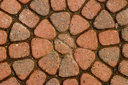 Red circular paved bricks with dirty moss and worn age Stockfoto