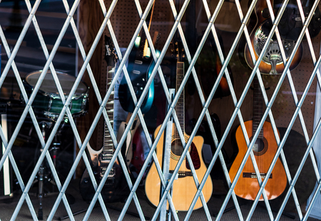 Pawn shop window covered by bars and musical instruments behind Editorial