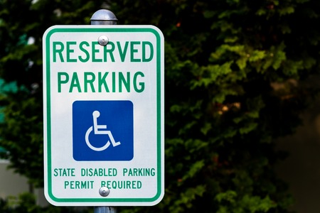 Reserved handicapped permit parking only sign in front of green bushes Stock Photo