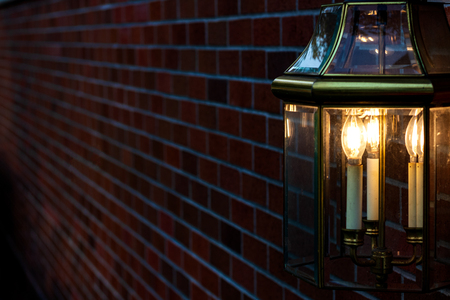 Lamp mounted on a brick wall illuminating golden light in the darkness Stock Photo