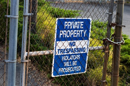 Blue private property no trespassing sign on a chain link fence with grass